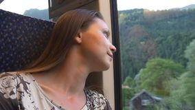 Sad woman sitting alone in a train. Melancholy. Thoughtful woman traveling by a comfortable train. She looks on summer landscape and dreaming stock video