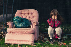 Sad woman sitting by armchair outside Stock Photo