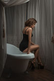 Sad woman sitting in a bathtub. Royalty Free Stock Image