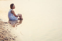 Sad woman sitting on the beach . Stock Photos