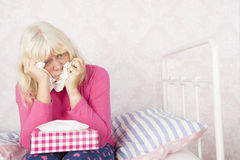 Sad woman sitting in bed Royalty Free Stock Photo