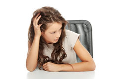 Sad woman sitting behind the desk Royalty Free Stock Image