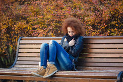Sad woman sitting on the bench in autumn park Stock Photos