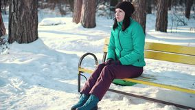 Sad woman sitting on a bench in winter time. Medium long shot stock footage