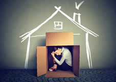 Sad woman sitting in box house in search for shelter. Stressed woman sitting in a box house in search for shelter royalty free stock photography