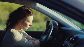 A sad woman is sitting in the car. Very upset. Depression, women`s problems. HD video stock video