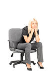 Sad woman sitting in a chair Stock Photo