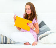 Sad woman sitting on couch and reading bad news Stock Photography