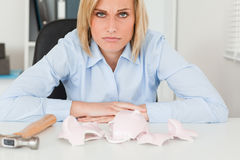 Sad woman sitting in front. Of an empty shattered piggy bank in her office Stock Images