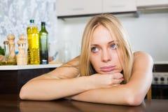 Sad   woman sitting at kitchen Stock Photography