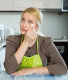 Sad woman sitting at kitchen. Lonely young blonde woman sitting sad at the table at home kitchen Stock Images
