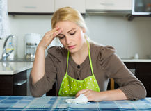 Sad woman sitting at kitchen Royalty Free Stock Photo