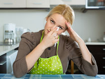 Sad woman sitting at kitchen. Unhappy lonely blonde girl sitting sad in kitchen at home Stock Image