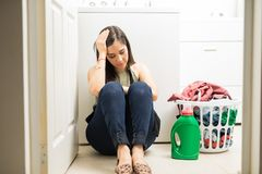 Sad woman sitting in laundry room with a pile of dirty clothes. Frustrated young woman sitting in front of washing machine with basket full of clothes Royalty Free Stock Images
