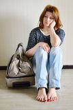 Sad woman sitting near the wall with suitcase because divorce Royalty Free Stock Photo