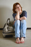 Sad woman sitting near the wall with suitcase because divorce Stock Images