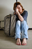 Sad woman sitting near the wall with suitcase because divorce. Sad woman sitting near the wall with a suitcase because divorce Royalty Free Stock Photo