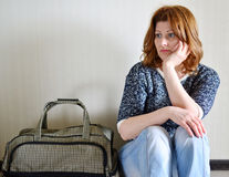 Sad woman sitting near the wall with suitcase because divorce Stock Photo