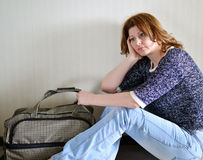 Sad woman sitting near the wall with suitcase because divorce Royalty Free Stock Image