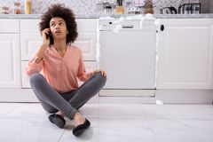 Sad Woman Sitting Next To Damaged Dishwasher Calling Technician. Sad Woman Calling Technician On Cellphone To Fix Dishwasher With Foam Coming Out From It stock image