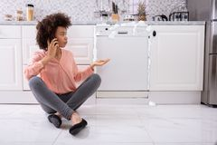 Sad Woman Sitting Next To Damaged Dishwasher Calling Technician. Sad Woman Calling Technician On Cellphone To Fix Dishwasher With Foam Coming Out From It royalty free stock photos