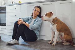 Free Sad Woman Sitting On A Kitchen Floor With Her Dog Stock Image - 120109881