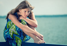 Sad woman sitting over sea at summer day stock photos