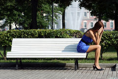 Sad woman sitting on a park bench Stock Images