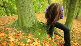 Sad woman sitting in park. Sad heartbroken woman sitting in the park outdoor, covers the face head by long brown hairs. Sadness in the solitude. Dolly sliding stock video footage