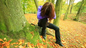Sad woman sitting in park. Sad heartbroken woman sitting in the park outdoor, covers the face head by long brown hairs. Sadness in the solitude. Dolly sliding stock footage