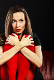 Sad woman sitting on red couch Royalty Free Stock Photos