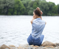 Sad woman sitting on rocks Royalty Free Stock Photography