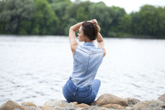 Sad woman sitting on rocks Royalty Free Stock Photo