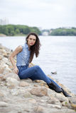 Sad woman sitting on rocks Stock Photos