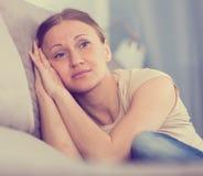 Sad woman sitting on sofa. Portrait of sad woman sitting on sofa in home interior stock photography