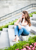 Sad woman sitting on steps Stock Photography