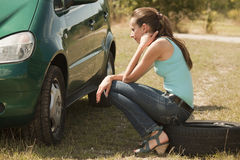 Sad woman sitting on tire Royalty Free Stock Photography