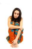Sad woman sitting on white background Royalty Free Stock Images