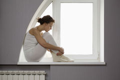 Sad Woman Sitting On Window Sill Royalty Free Stock Photography
