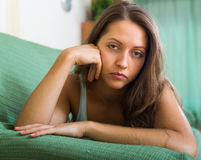 Sad woman on sofa in home Royalty Free Stock Photography