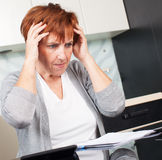 Sad woman sorting through her old receipts Royalty Free Stock Photo