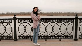 Sad woman standing in autumn in front of metal fence on river embankment and looking at view 4K stock video