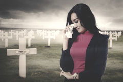Sad woman standing in the graveyard Royalty Free Stock Photo
