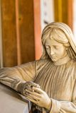 Sad woman. Statue of sad woman looking down with  hands together in prayer Stock Photo