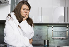 Sad woman suffering from toothache standing in kitchen Royalty Free Stock Images