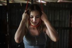 Sad woman suicide by  rope hanging. Stressed Asian beautiful Woman holding red rope to her neck to suicide by hanging in abandon house. Depression, death Royalty Free Stock Image
