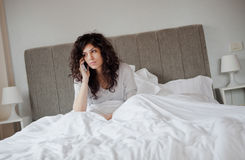 Sad woman talking on the phone. In the morning from her bed Royalty Free Stock Photo
