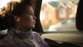 Sad woman in a taxi and looking out the window. Girl riding in a taxi and looking at the phone