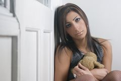 Sad woman with teddy bear. A sad young woman, sitting and holding a soft teddy bear Royalty Free Stock Photo