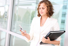 Sad Woman Texting. A pretty caucasian woman texting at her office building looking sad stock photos